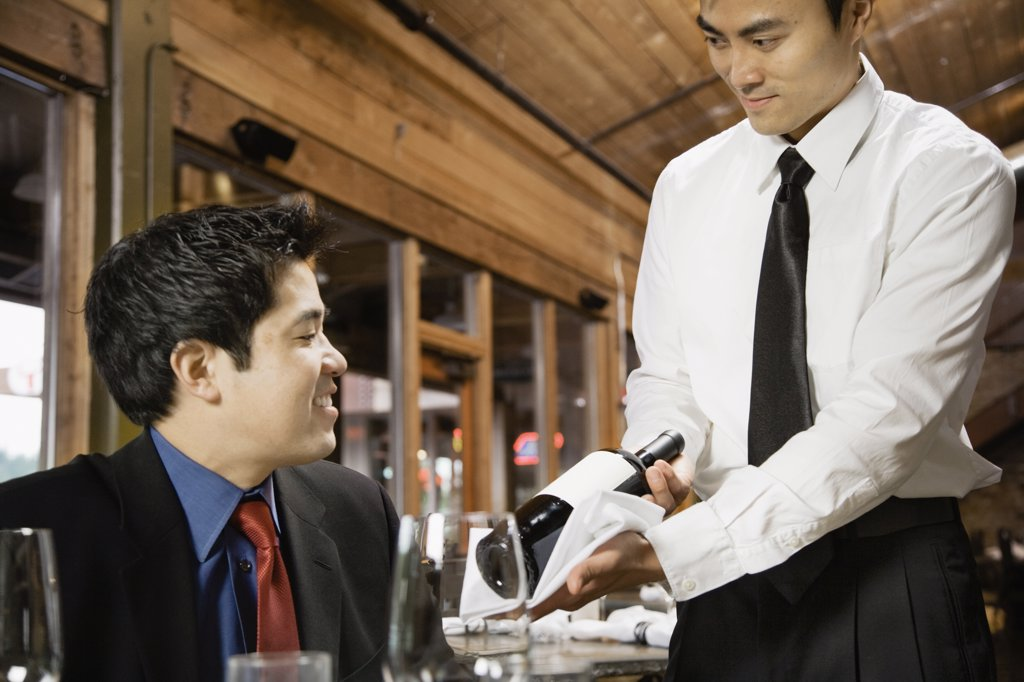 Asian waiter showing wine to customer : Stock Photo