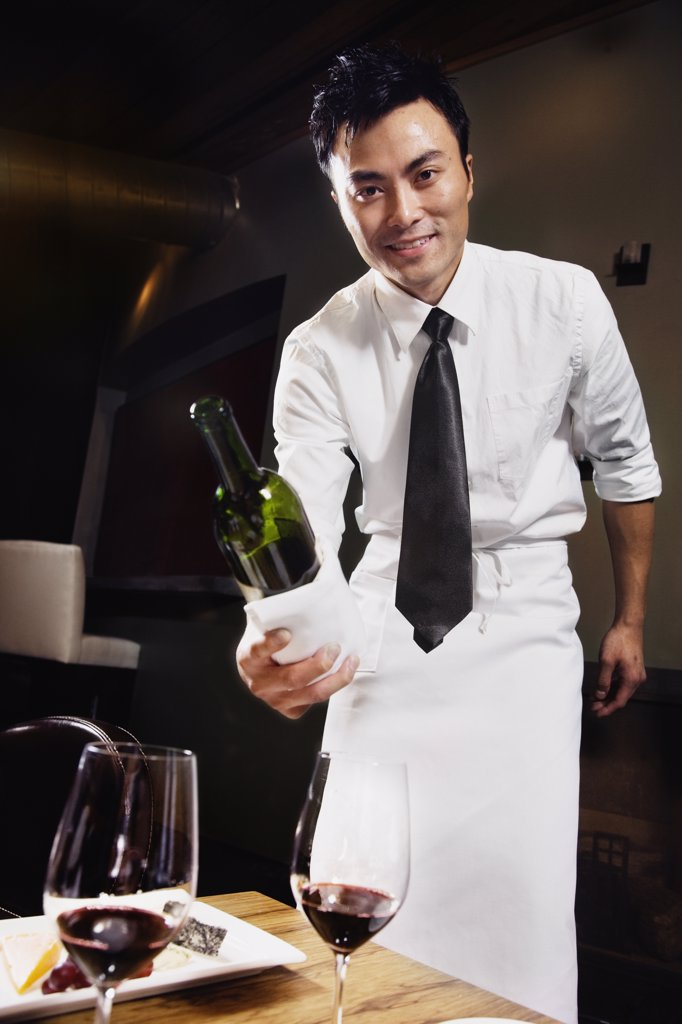 Stock Photo: 1589R-59787 Asian waiter pouring wine