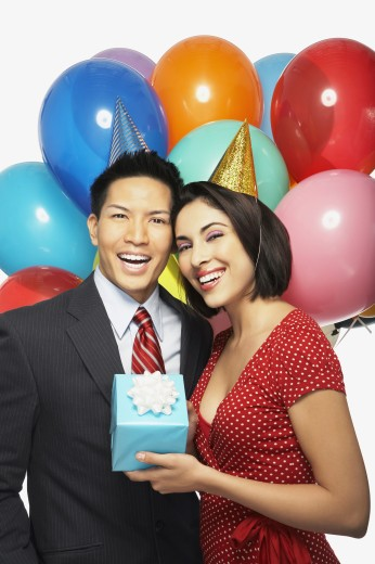 Multi-ethnic couple wearing party hats : Stock Photo