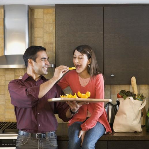 Stock Photo: 1589R-59879 Hispanic father feeding fruit to daughter