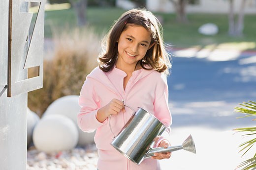 Hispanic girl holding watering can : Stock Photo