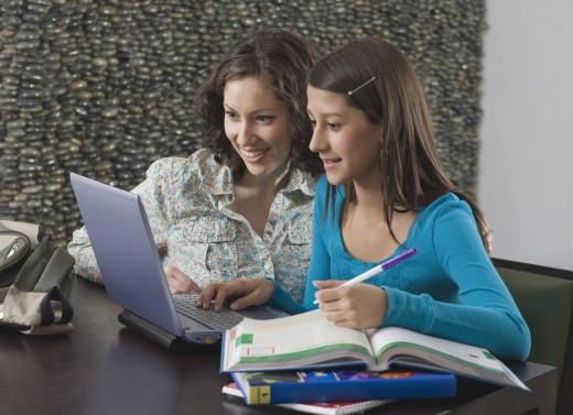 Hispanic mother helping daughter with homework : Stock Photo