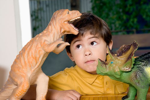 Stock Photo: 1589R-59982 Hispanic boy playing with toy dinosaurs
