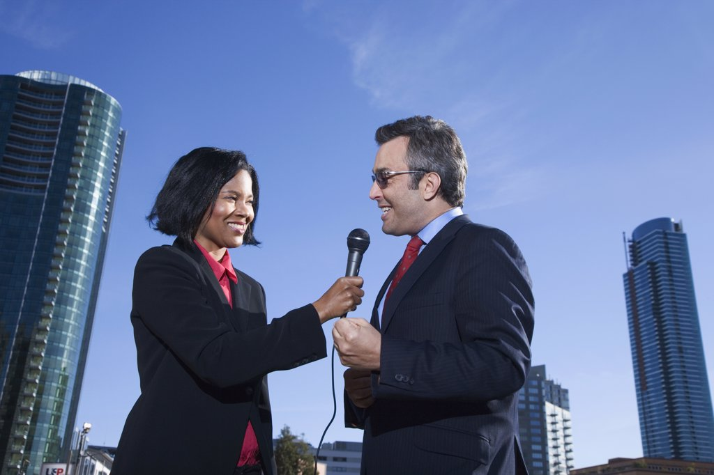 Stock Photo: 1589R-60044 African female reporter interviewing businessman