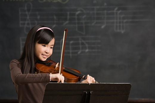 Stock Photo: 1589R-60177 Asian girl playing violin in front of blackboard