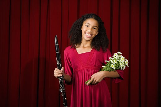 Stock Photo: 1589R-60277 Mixed Race girl holding clarinet and flowers on stage