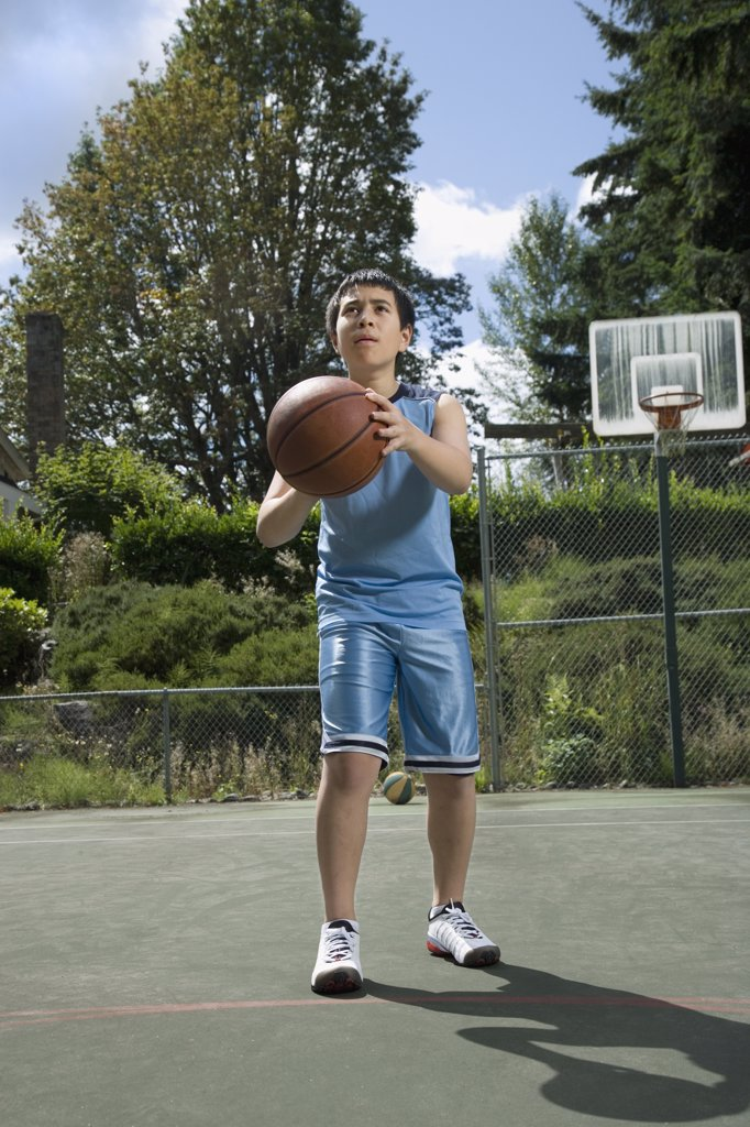 Stock Photo: 1589R-60321 Asian boy playing basketball