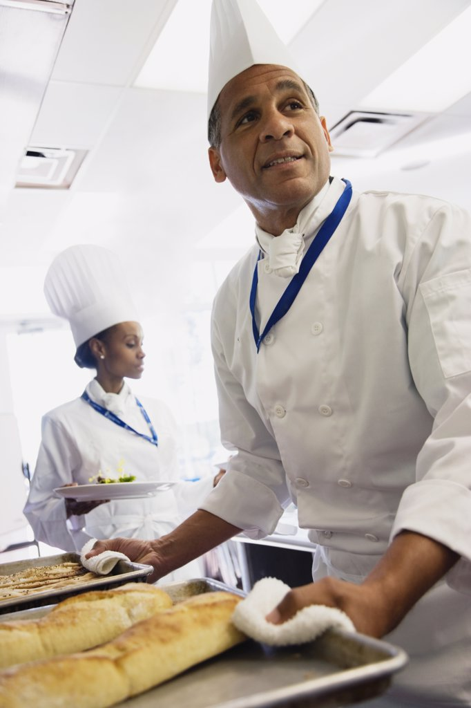 Stock Photo: 1589R-60405 Multi-ethnic chefs carrying food in kitchen