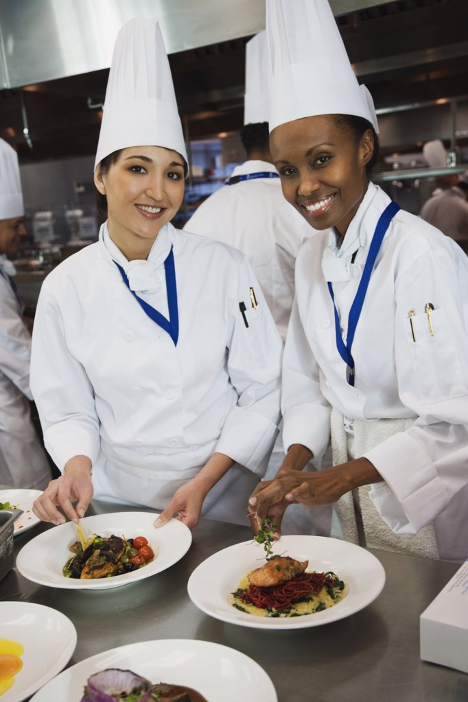 Multi-ethnic female chefs garnishing plates of food : Stock Photo