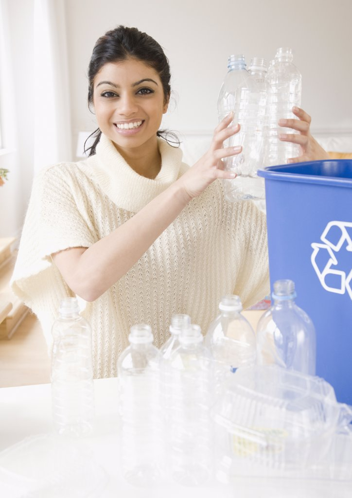 Mixed Race woman filling recycling bin : Stock Photo