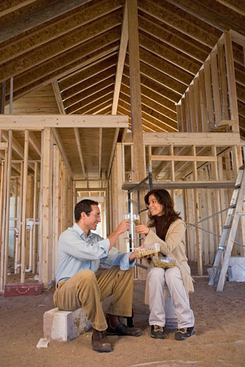 Stock Photo: 1589R-60556 Hispanic couple toasting champagne at new construction site