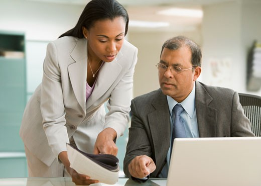 Multi-ethnic businesspeople looking at paperwork : Stock Photo
