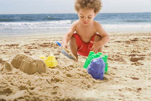 Mixed Race baby playing at beach : Stock Photo