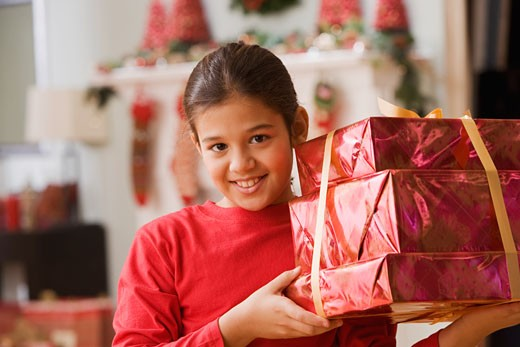 Stock Photo: 1589R-60808 Hispanic girl holding stack of Christmas gifts
