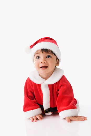 Hispanic baby wearing Santa Claus suit : Stock Photo