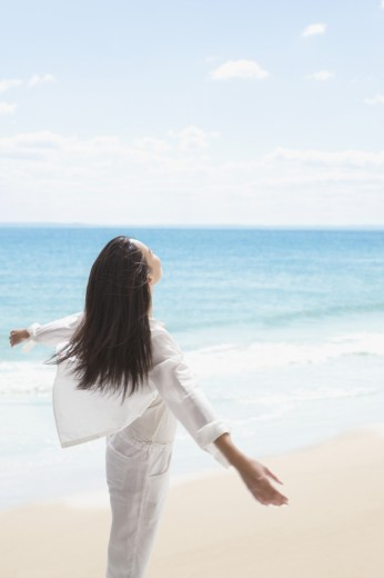 Stock Photo: 1589R-60866 Asian woman with arms outstretched on beach