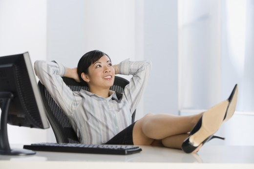 Asian businesswoman with feet on desk : Stock Photo