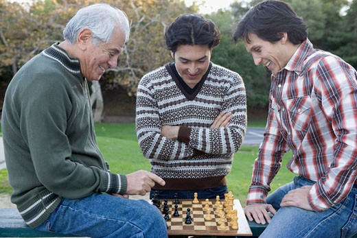 Stock Photo: 1589R-61048 Hispanic grandfather playing chess with grandson