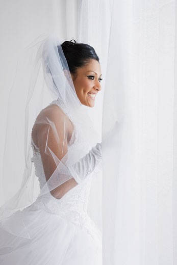 Hispanic bride looking out window : Stock Photo
