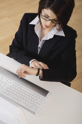Hispanic businesswoman looking at watch : Stock Photo