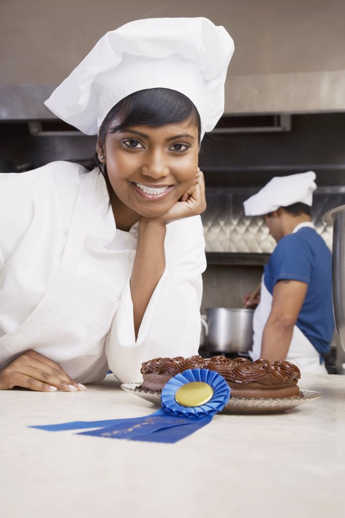Stock Photo: 1589R-61210 Mixed Race female pastry chef with blue ribbon and cake