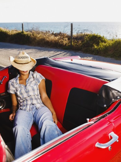 Stock Photo: 1589R-61264 Mixed race woman sleeping in back of red convertible