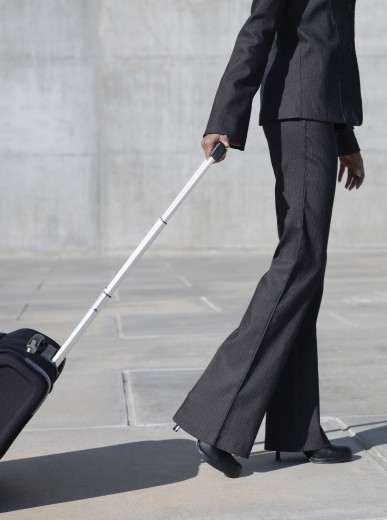 Indian businesswoman pulling rolling luggage : Stock Photo