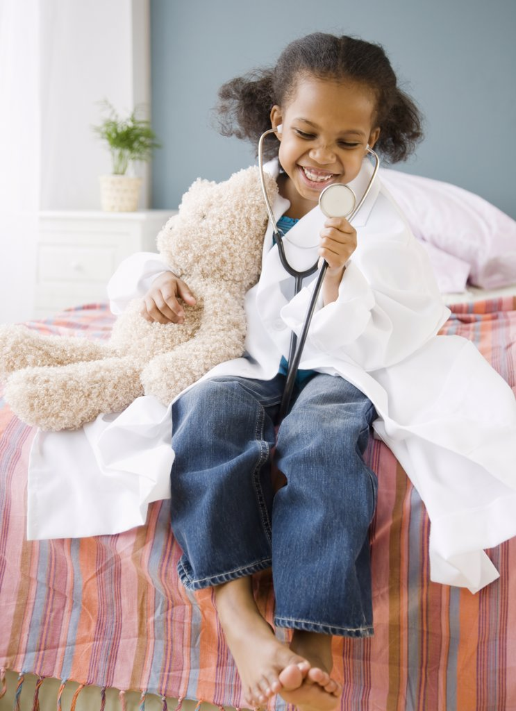 Stock Photo: 1589R-61412 Mixed race girl playing doctor with teddy bear