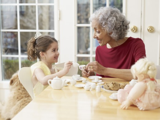 Hispanic grandmother having tea party with granddaughter : Stock Photo