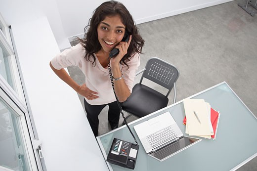 Trinidadian businesswoman talking on telephone in office : Stock Photo