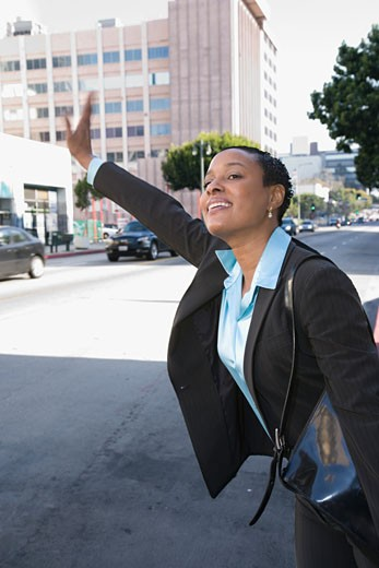 Stock Photo: 1589R-61605 African businesswoman hailing a taxi