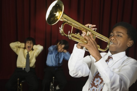 African boy playing trumpet with multi-ethnic classmates covering ears : Stock Photo