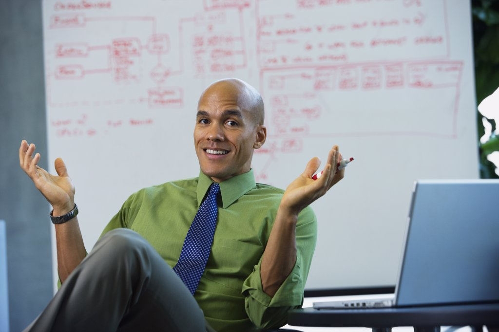 Mixed race businessman smiling and gesturing in office : Stock Photo