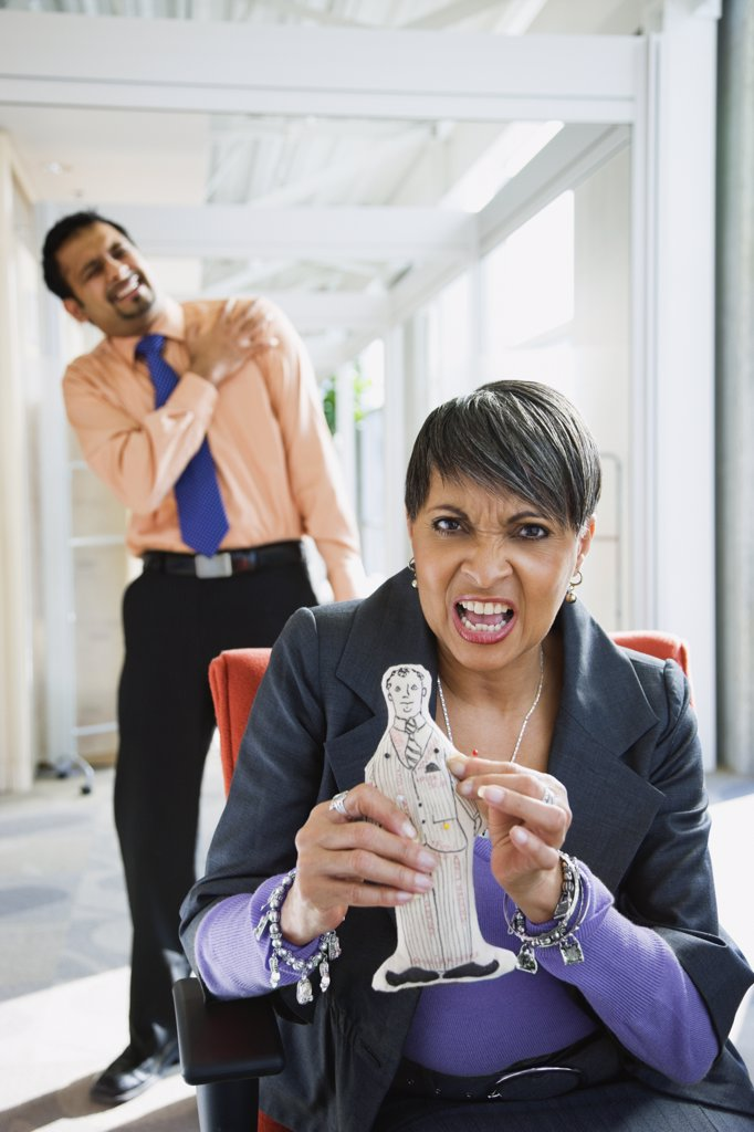 Angry African businesswoman holding voodoo doll of co-worker : Stock Photo