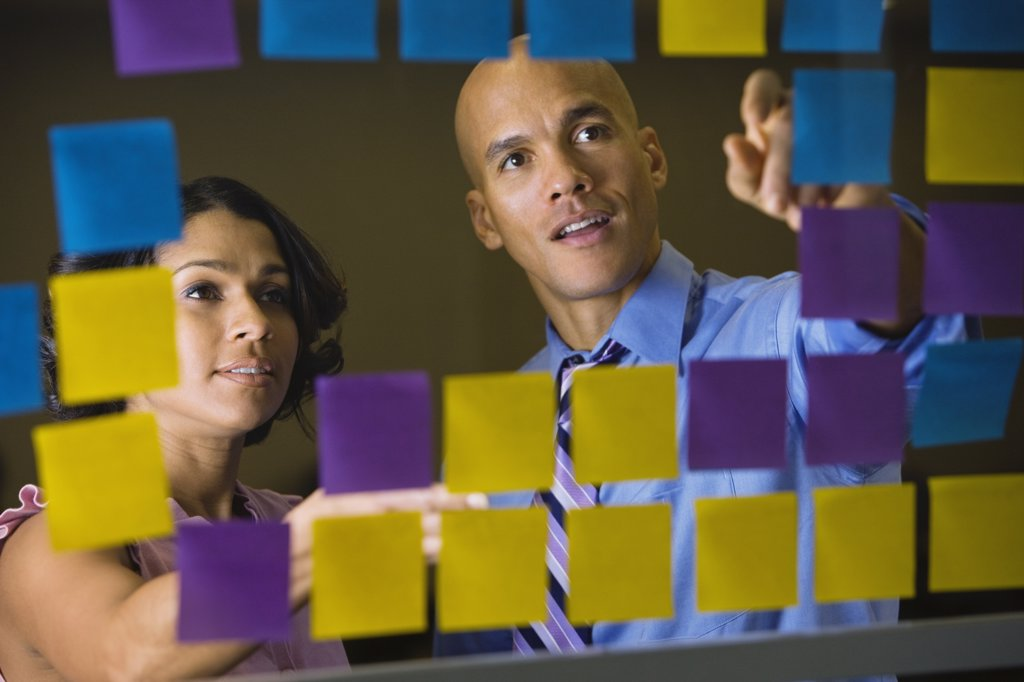 Multi-ethnic business people reviewing sticky notes : Stock Photo