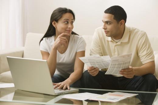 Hispanic couple paying bills online : Stock Photo