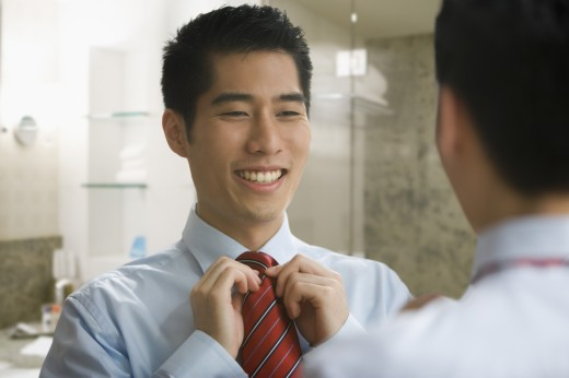 Korean businessman adjusting tie in mirror : Stock Photo