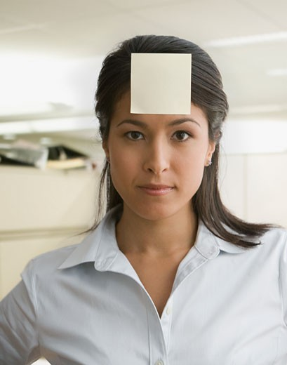 Stock Photo: 1589R-62142 Eurasian businesswoman with sticky note on forehead