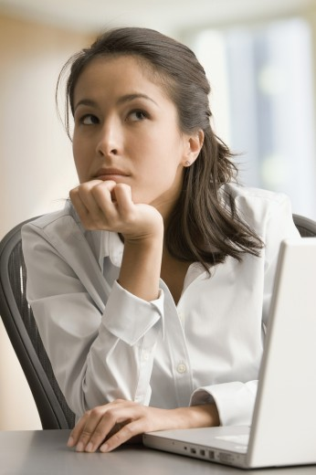 Stock Photo: 1589R-62169 Eurasian businesswoman looking pensive