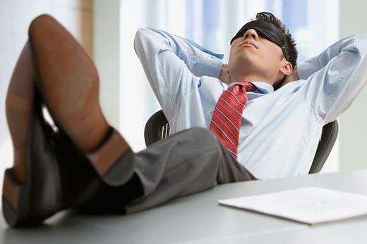 Korean businessman with feet up sleeping at desk : Stock Photo