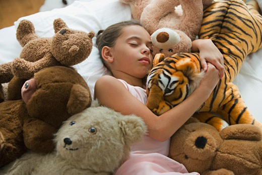 Stock Photo: 1589R-62188 Hispanic girl sleeping in bed surrounded by stuffed animals