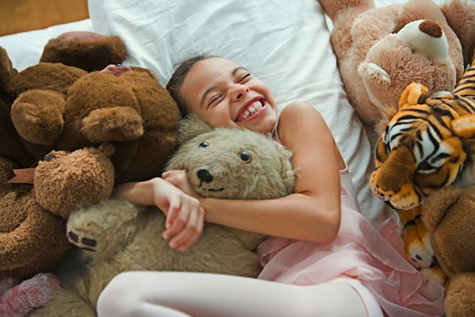 Hispanic girl hugging teddy bear in bed : Stock Photo