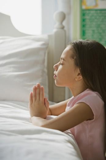 Stock Photo: 1589R-62193 Hispanic girl praying in bedroom