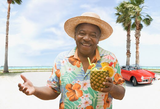 Stock Photo: 1589R-62213 African man holding pineapple drink on tropical beach
