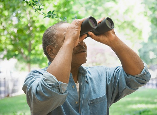 African man looking through binoculars outdoors : Stock Photo