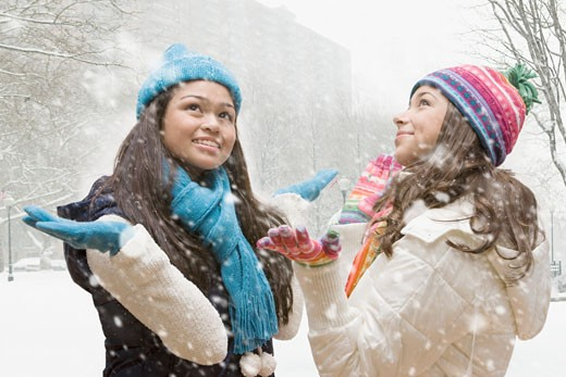 Multi-ethnic girls looking up in snow : Stock Photo