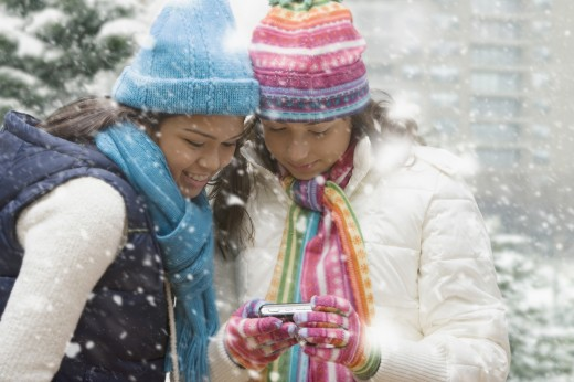 Stock Photo: 1589R-62311 Multi-ethnic girls in snow holding digital camera