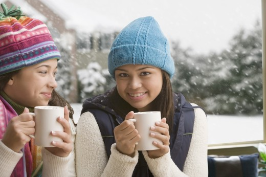 Multi-ethnic girls in snow drinking hot cocoa : Stock Photo