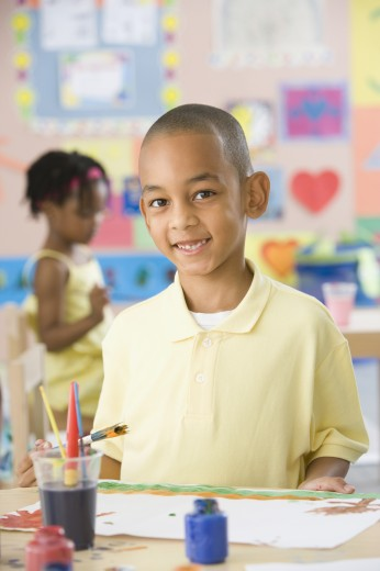 African boy painting in classroom : Stock Photo