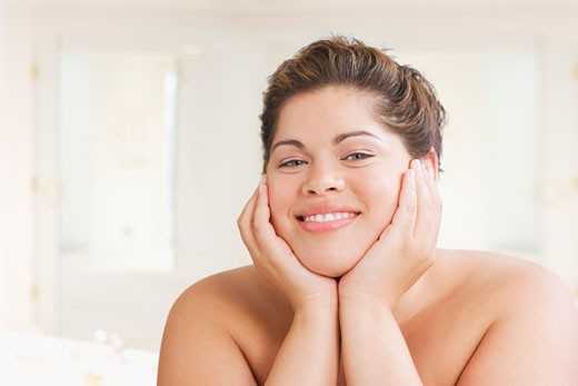Hispanic woman smiling with head in hands : Stock Photo